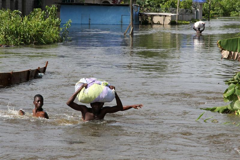 People wade through a flood with their belongings after their houses were submerged in the Amassoma community in Bayelsa state October 6, 2012. REUTERS/Tife Owolabi